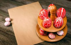Easter red eggs with folk white pattern lay around stand for eggs which stand on rustic wood background. Top view. Ukrainian tradi. Tional eggs pisanka and royalty free stock image