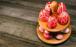 Easter red eggs with folk white pattern lay around stand for eggs which stand on rustic wood background. Top view. Ukrainian tradi. Tional eggs pisanka and stock image