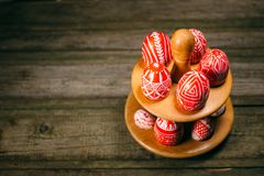 Easter red eggs with folk white pattern lay around stand for eggs which stand on rustic wood background. Ukrainian traditional egg. S pisanka and krashanka royalty free stock photo