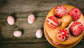 Easter red eggs with folk white pattern lay around stand for eggs which stand on rustic wood background and eggs scattered. Ukrain. Ian traditional eggs pisanka royalty free stock photo