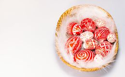Easter red eggs with folk white pattern lay on feather into basket on white background, top view. Ukrainian traditional eggs Stock Image