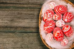 Easter red eggs with folk white pattern lay on feather into basket in the right side of rustic wood table. Ukrainian traditional e. Ggs pisanka and krashanka stock photography