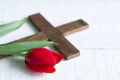Easter red tulip and cross on white boards. Closeup Royalty Free Stock Image
