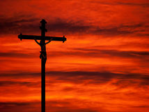 Easter religious background - crucifixion and sunset red sky. Church statue in front of spectacular red sky Stock Photo