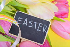 Easter ribbon, tulips and small blackboard Royalty Free Stock Image