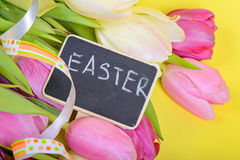 Easter ribbon, tulips and small chalkkboard Stock Image