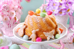Easter ring cake with candy eggs and cookies on spring table Stock Photo