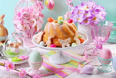 Easter ring cake with candy eggs and cookies on spring table Stock Photography