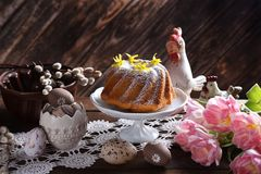Easter ring cake with powdered sugar in rustic style. Easter ring cake with powdered sugar and forsythia flowers on the top on festive table in rustic style stock photos