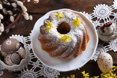 Easter ring cake with powdered sugar in rustic style. Top view of easter ring cake with powdered sugar on festive table in rustic style stock image