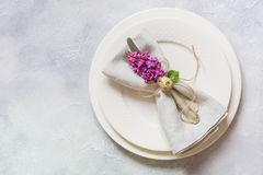 Easter romantic dinner. Elegance table setting with lilac flowers on light table. Top view. Elegance table setting with lilac flowers on light table. Easter royalty free stock photography