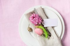 Easter dinner. Elegance table setting spring pink flowers on pink linen tablecloth. Top view. Easter romantic dinner. Elegance table setting spring pink flowers Stock Photos