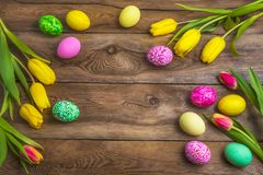 Easter rustic background with pink, yellow and green painted eggs royalty free stock photo