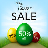 Easter sale banner with three eggs of different sizes on path in green field. Three eggs of different colors green, yellow,red and sizes on path in field with Royalty Free Stock Photos