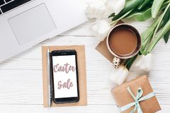 Easter sale on empty phone screen and laptop with morning coffee royalty free stock photography
