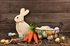 Easter scene with bunny, carrots and basket of eggs over wood Stock Photo