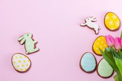 Easter scene with colored eggs. Eater handmade cookies with tulip flowers bouquet on pink background, flat lay top view frame with copy space stock images