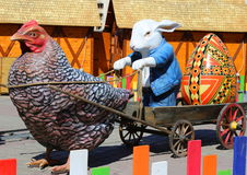 Easter scene. Rabbit and chicken harnessed to the cart Royalty Free Stock Photos