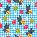 Easter seamless wallpaper. Easter bunny with flowers and Easter egg on checkered background. Beautiful vector festive seamless pattern Royalty Free Stock Image