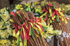 Easter season - flowers and sticks. Easter sticks with red green and yellow ribons, yellow easter flowers, placed outside a shop in Europe stock photography