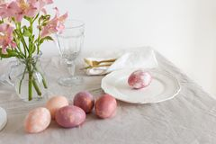 Easter serving plate with pink Easter eggs, gold tableware, glass and flowers on linen tablecloth in the morning royalty free stock photos
