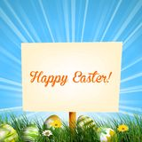 Easter sign background in meadow with sun rays and Easter eggs in the grass Royalty Free Stock Images