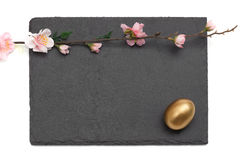 Easter Slate board with flowers and Golden Egg Stock Image