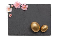 Easter Slate board with flowers and Golden Egg Stock Images