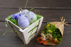 Easter small basket with colored eggs and a bunch of spring flowers on grey wooden board. Royalty Free Stock Image
