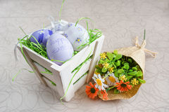 Easter small basket with colored eggs and a bunch of spring flowers on white board. Stock Image
