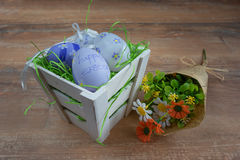 Easter small basket with colored eggs and a bunch of spring flowers on wooden board. Royalty Free Stock Photo