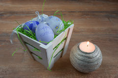 Easter small basket with colored eggs and a burning candle on wooden board. Stock Images