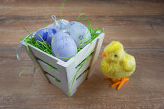 Easter small basket with colored eggs and a small chicken on wooden board. Royalty Free Stock Photos