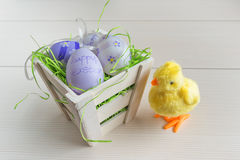 Easter small basket with colored eggs and a small chicken on wooden board. Royalty Free Stock Images