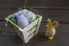 Easter small basket with colored eggs and a small egg rabbit on grey wooden board. Stock Images