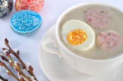 Easter soup with egg and white sausage. On table. Pysanky and willow branches in the background stock image