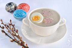 Easter soup with egg and white sausage. On table. Pysanky and willow branches in the background stock images