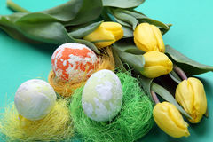 Easter speckled eggs in sockets and yellow tulips Stock Image