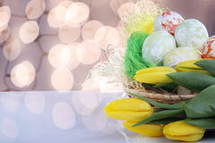 Easter speckled eggs in sockets and yellow tulips with space for Royalty Free Stock Image
