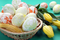 Easter speckled eggs and tulips in a basket Stock Photos