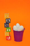 Easter spelled with alphabet blocks and a bucket of eggs Stock Image