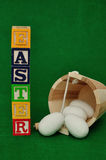 Easter spelled with alphabet blocks and a bucket of eggs Stock Photography
