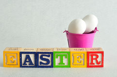 Easter spelled with alphabet blocks and a bucket of eggs Royalty Free Stock Photography