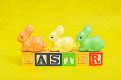 Easter spelled with alphabet blocks and a colorful bunnies Stock Images