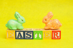 Easter spelled with alphabet blocks and a colorful bunnies Royalty Free Stock Photography