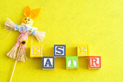 Easter spelled with alphabet blocks and a scarecrow bunny Royalty Free Stock Photo