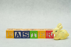 Easter spelled with alphabet blocks and a yellow bunny Royalty Free Stock Photos