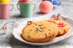 Easter Spring Cookies with colorful sprinkles on a white plate. Easter happy concept royalty free stock photo