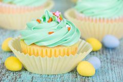 Easter spring cupcake with candy eggs. And sprinkles on wooden green table Royalty Free Stock Photo