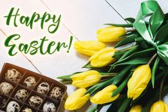 Easter spring decorative composition. Bouquet of yellow tulips tied by green ribbon and little box with quail eggs. Close up portr. Ait on white wooden Royalty Free Stock Photos